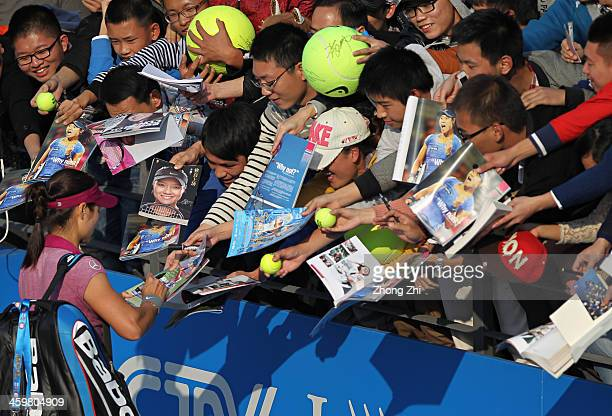 Na Li of China signs autographs for fans after winning her match against Vera Zvonareva of Russia on day four of the WTA Shenzhen Open at Shenzhen...
