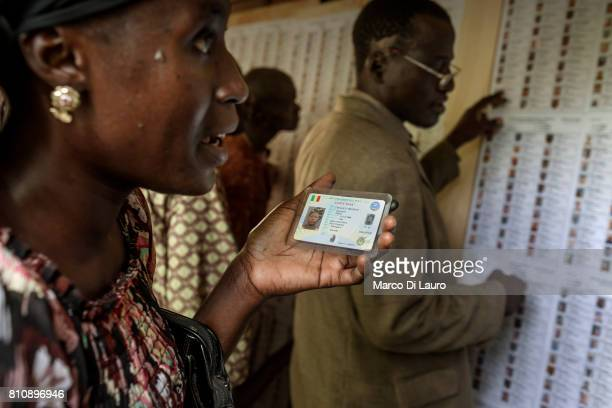 NA Malian woman is seen holding her ID at a pooling station as she checks the electoral list during the first round of the Presidential election on...