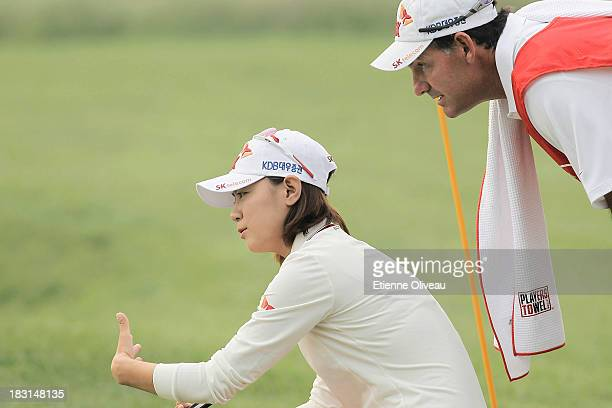 Na Yeon Choi of South Korea discusses her next putt with her caddie during the third round of the Reignwood LPGA Classic at Pine Valley Golf Club on...