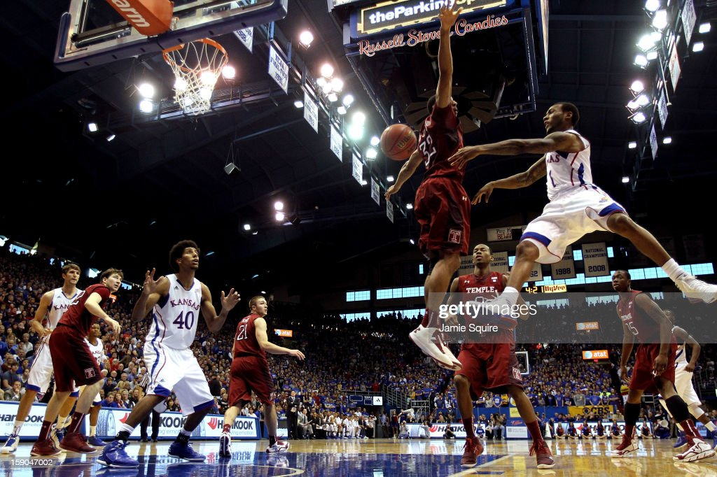Naadir Tharpe #1 of the Kansas Jayhawks passes Temple Owls Kevin Young #40 during the game against the Temple Owls at Allen Fieldhouse on January 6, 2013 in Lawrence, Kansas.