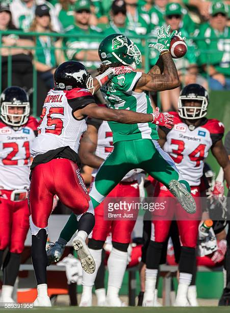 Naaman Roosevelt of the Saskatchewan Roughriders leaps to make a catch in front of Tommie Campbell of the Calgary Stampeders in first half action of...