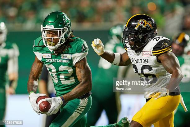 Naaman Roosevelt of the Saskatchewan Roughriders runs past Cariel Brooks of the Hamilton TigerCats after making a catch in the game between the...