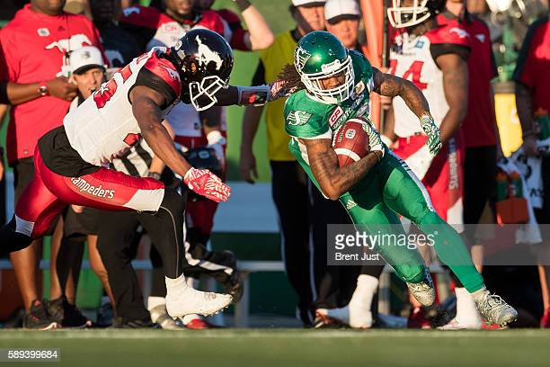 Naaman Roosevelt of the Saskatchewan Roughriders runs past Tommie Campbell of the Calgary Stampeders after a catch in the game between the Calgary...