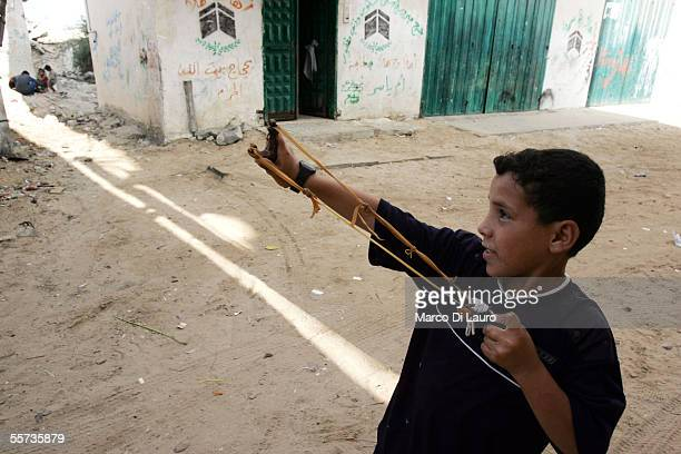 Nabel Mokhemar fiveyearsold plays with a sling shot toy while standing in front of his house on September 21 2005 in the Khan Younis refugee camp...
