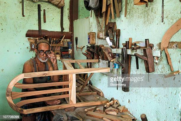 Nabi Jaan a carpenter pauses while making a chair in a furniture making workshop in Mumbai India on Wednesday Nov 10 2010 Building companies...