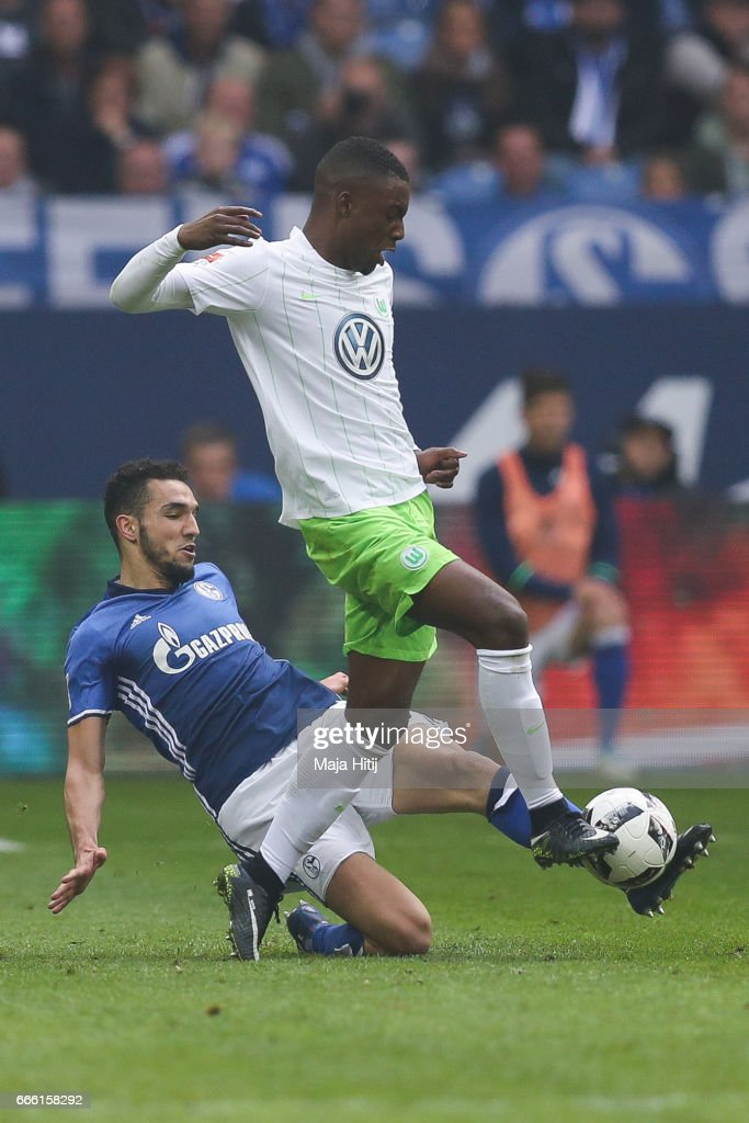 Nabil Bentaleb of Schalke (L) and Richedly Bazoer of Wolfsburg battle for the ball during the Bundesliga match between FC Schalke 04 and VfL Wolfsburg at Veltins-Arena on April 8, 2017 in Gelsenkirchen, Germany.