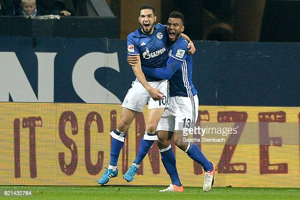 Nabil Bentaleb of Schalke celebrates with team mate Eric Maxim ChoupoMoting after scoring his team's second goal during the Bundesliga match between...