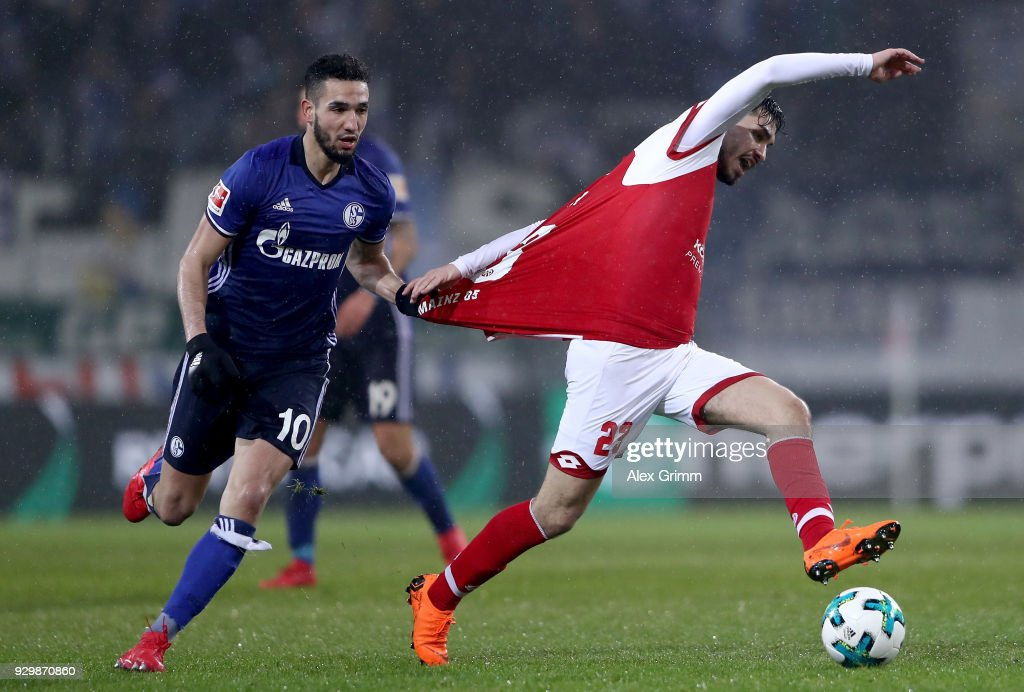 Nabil Bentaleb of Schalke holds Suat Serdar of Mainz during the Bundesliga match between 1. FSV Mainz 05 and FC Schalke 04 at Opel Arena on March 9, 2018 in Mainz, Germany.