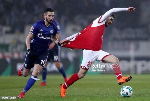 Nabil Bentaleb of Schalke holds Suat Serdar of Mainz during the Bundesliga match between 1 FSV Mainz 05 and FC Schalke 04 at Opel Arena on March 9...