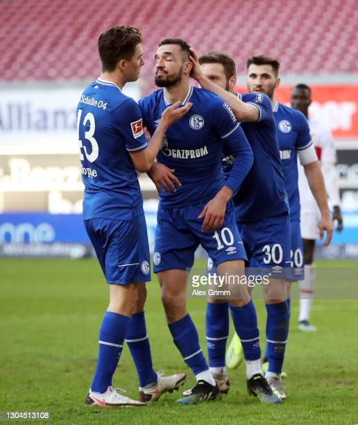 Nabil Bentaleb of Schalke is consoled by team mates Matthew Hoppe, Shkodran Mustafi and Sead Kolasinac after he had missed a penalty during the...