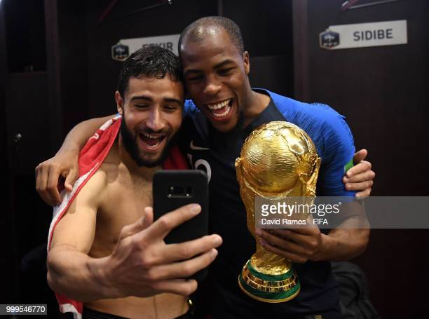 Nabil Fekir of France and Djibril Sidibe of France celebrate with the World Cup Trophy in the dressing room following their sides victory in the 2018...