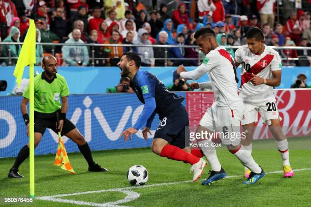 Nabil Fekir of France is fouled by Miguel Trauco and Edison Flores of Peru during the 2018 FIFA World Cup Russia group C match between France and...