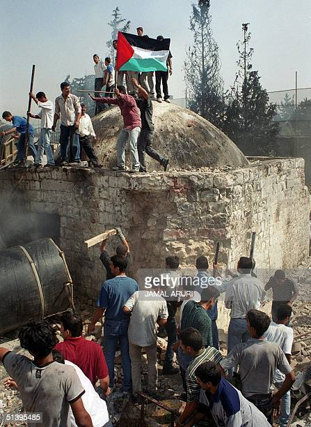 Palestinian protesters destroy the site of Joseph's Tomb in the West Bank town of Nablus 07 October 2000. After Israeli army vacated at dawn the site...