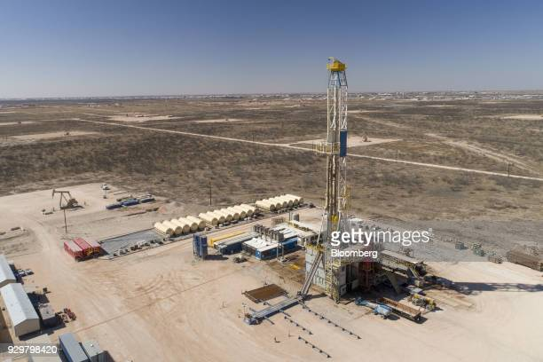 A Nabors Industries Ltd drill rig stands over an oil well for Chevron Corp in the Permian Basin in this aerial photograph taken over Midland Texas US...