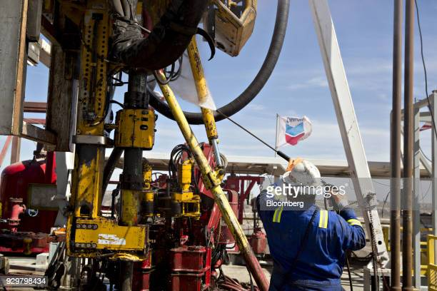 A Nabors Industries Ltd roughneck uses a power washer to clean the drilling floor of a rig drilling for Chevron Corp in the Permian Basin near...