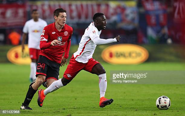 Naby Deco Keita of Leipzig and Gaetan Bussmann of Mainz vie during the Bundesliga match between RB Leipzig and 1 FSV Mainz 05 at Red Bull Arena on...