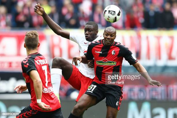Naby Deco Keita of Leipzig and Karim Guede of Freiburg compete for the ball during the Bundesliga match between RB Leipzig and SC Freiburg at Red...