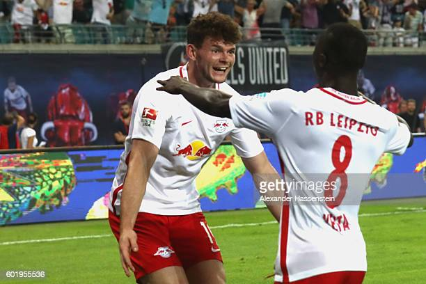 Naby Deco Keita of Leipzig celebrates scoring the first goal with his team mate Oliver Jasen Burke during the Bundesliga match between RB Leipzig and...