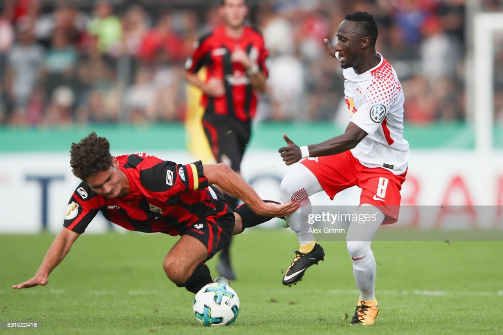 Naby Keita of Leipzig is challenged by Niklas Weissenberger of Dorfmerkingen during the DFB Cup first round match between Sportfreunde Dorfmerkingen and RB Leipzig at Ostalb-Arena on August 13, 2017 in Aalen, Germany.