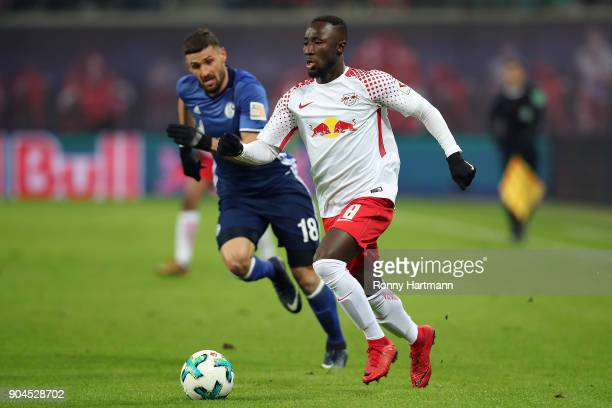 Naby Keita of Leipzig is chased by Daniel Caligiuri of Schalke during the Bundesliga match between RB Leipzig and FC Schalke 04 at Red Bull Arena on...