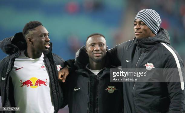 Naby Keita of Leipzig is hugged by Jean Kevin Augustin and goalkeeper Yvon Mvogo of Leipzig after the Bundesliga match between RB Leipzig and FC...