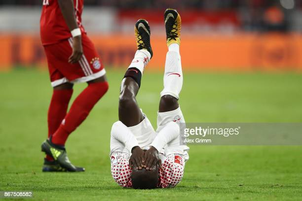 Naby Keita of Leipzig lies on the pitch in pain during the Bundesliga match between FC Bayern Muenchen and RB Leipzig at Allianz Arena on October 28...