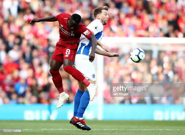 Naby Keita of Liverpool battles for posession in the air with Dale Stephens of Brighton and Hove Albion during the Premier League match between...