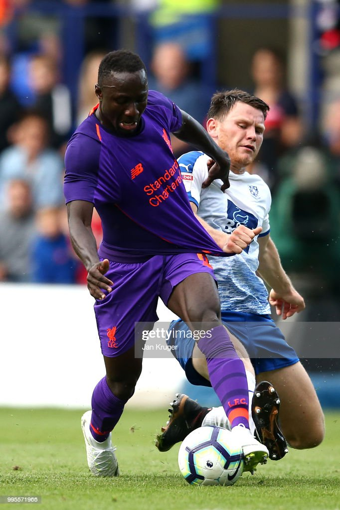 Naby Keita of Liverpool battles with Connor Jennings of Tranmere Rovers during the Pre-Season Friendly match between Tranmere Rovers and Liverpool at Prenton Park on July 11, 2018 in Birkenhead, England.