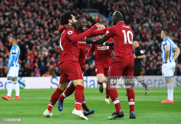 Naby Keita of Liverpool celebrates after scoring his team's first goal with Mohamed Salah and Sadio Mane during the Premier League match between...
