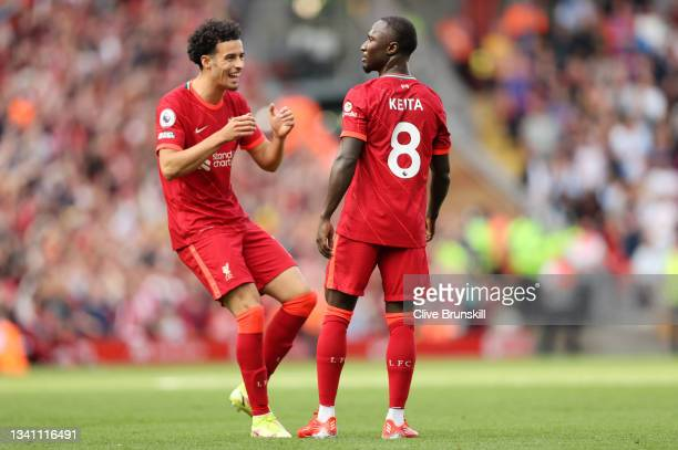 Naby Keita of Liverpool celebrates with teammate Curtis Jones after scoring their team's third goal during the Premier League match between Liverpool...