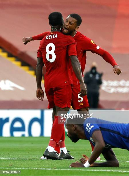 Naby Keita of Liverpool celebrates with teammate Georginio Wijnaldum after scoring his team's first goal during the Premier League match between...