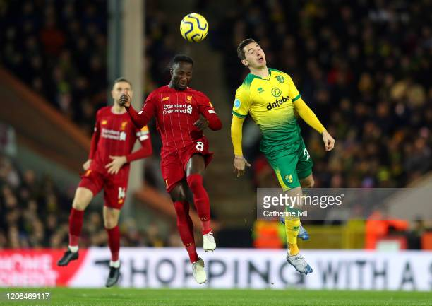 Naby Keita of Liverpool competes for a header with Kenny McLean of Norwich City during the Premier League match between Norwich City and Liverpool FC...