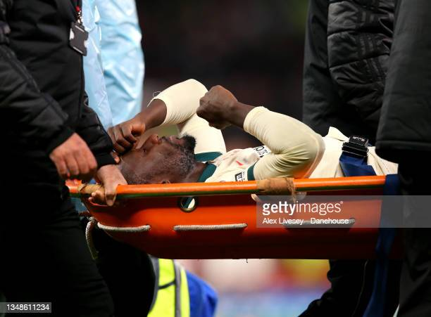 Naby Keita of Liverpool goes off injured after a collision with Paul Pogba of Manchester United during the Premier League match between Manchester...