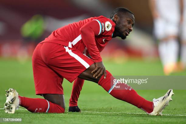 Naby Keita of Liverpool holds his leg following an injury during the Premier League match between Liverpool and Leicester City at Anfield on November...