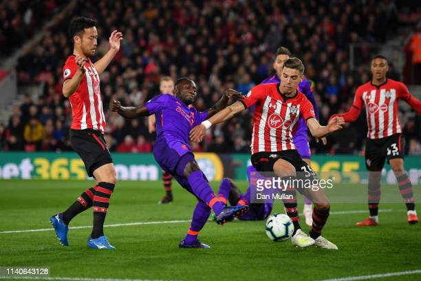 Naby Keita of Liverpool shoots while challenged by Jan Bednarek of Southampton during the Premier League match between Southampton FC and Liverpool...