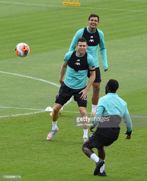Naby Keita of Liverpool with James Milner of Liverpool and Dejan Lovren of Liverpool during a training session at Melwood Training Ground on June 19...