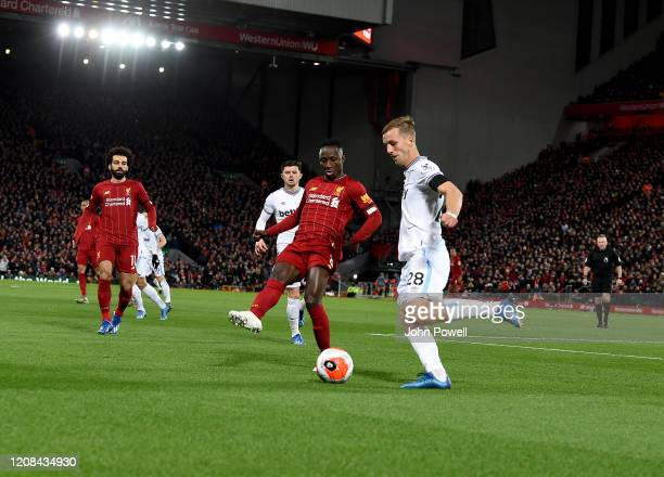 Naby Keita of Liverpool with Thomas soucek during the Premier League match between Liverpool FC and West Ham United at Anfield on February 24 2020 in...