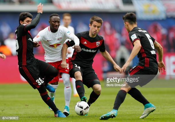Naby Keita of RB Leipzig is challenged by Almog Cohen Stefan Lex and Alfredo Morales of FC Ingolstadt 04 durin the Bundesliga match between RB...