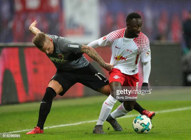 Naby Keita of RB Leipzig is challenged by Jonathan Schmid of FC Augsburg during the Bundesliga match between RB Leipzig and FC Augsburg at Red Bull...