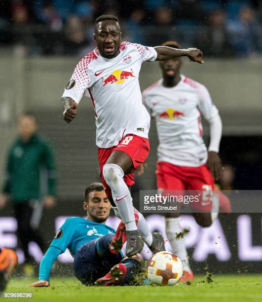 Naby Keita of RB Leipzig is tackled by Emanuel Mammana during UEFA Europa League Round of 16 match between RB Leipzig and Zenit St Petersburg at the...
