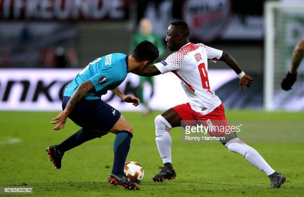 Naby Keita of RB Leipzig vies with Matas Kranevitter of FC Zenit Saint Petersburg during the UEFA Europa League Round of 16 match between RB Leipzig...