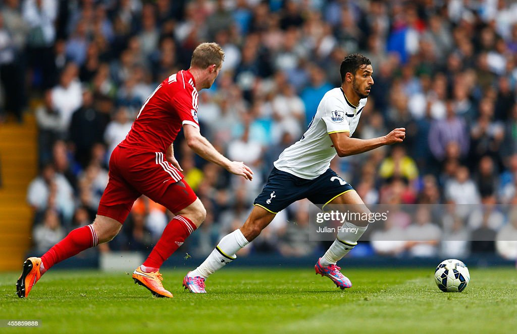 Nacer Chadli of Spurs is pursued by Chris Brunt of West Brom during the Barclays Premier League match between Tottenham Hotspur and West Bromwich Albion at White Hart Lane on September 21, 2014 in London, England.