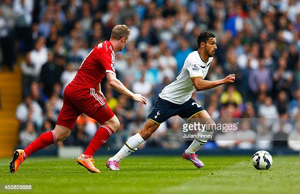 Nacer Chadli of Spurs is pursued by Chris Brunt of West Brom during the Barclays Premier League match between Tottenham Hotspur and West Bromwich...
