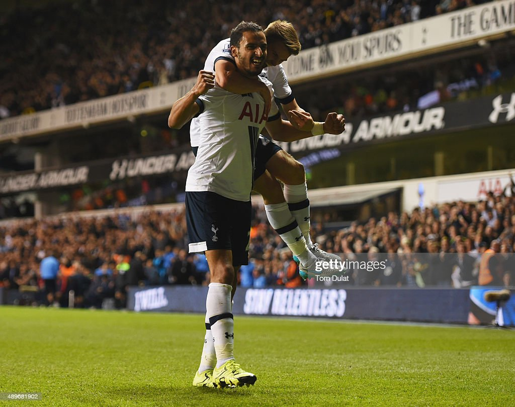 Nacer Chadli of Tottenham Hotspur (front) celebrates with Tommy Carroll as Calum Chambers of Arsenal scores an own goal foe their first goal during the Capital One Cup third round match between Tottenham Hotspur and Arsenal at White Hart Lane on September 23, 2015 in London, England.