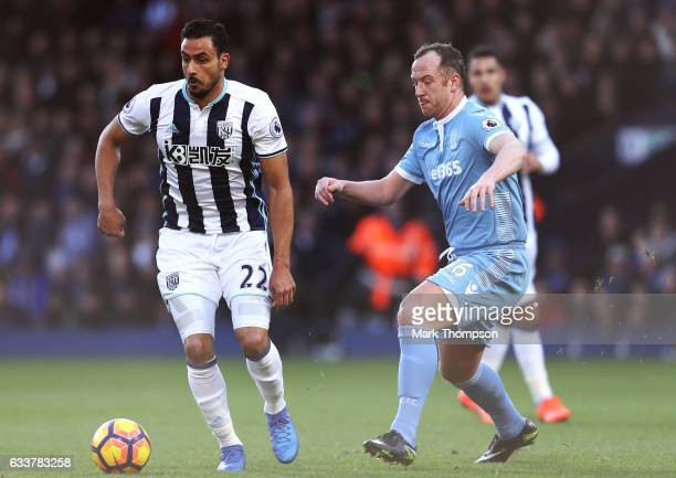 Nacer Chadli of West Bromwich Albion and Charlie Adam of Stoke City compete for the ball during the Premier League match between West Bromwich Albion...