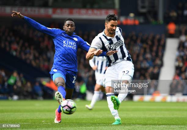 Nacer Chadli of West Bromwich Albion shoots under pressure from Wilfred Ndidi of Leicester City during the Premier League match between West Bromwich...