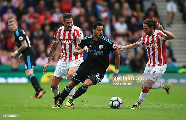 Nacer Chadli of West Bromwich Albion takes it past Joe Allen of Stoke City during the Premier League match between Stoke City and West Bromwich...