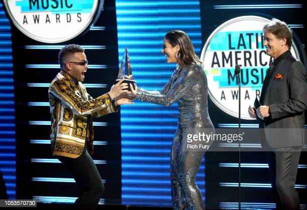 Nacho accepts the Favorite Tropical Song award for 'Bailame' from Gaby Espino and Guy Ecker onstage during the 2018 Latin American Music Awards at...