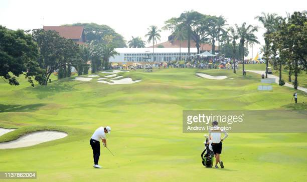 Nacho Elvira of Spain plays his second shot on the second hole as his caddie Diego Suazo looks on during Day Four of the Maybank Championship at...