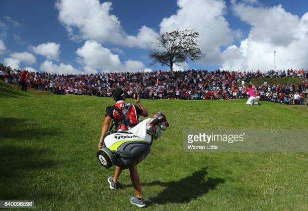 Nacho Elvira of Spain salutes the crowd as he walks onto the 16th green while his caddie videos during the final round of the Made in Denmark at...
